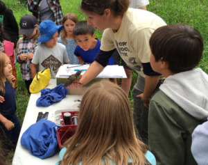 Avian biologist Lauren Walker demonstrating banding to summer campers